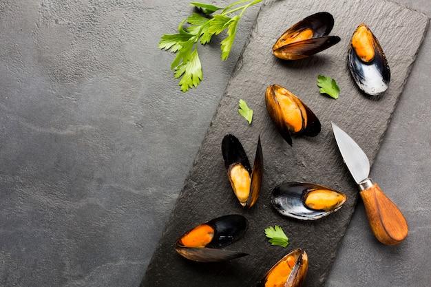 Moules cuites à plat sur une ardoise avec fond Photo gratuit