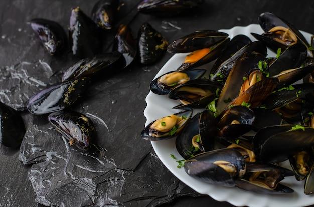 Moules fraîches crues et cuites sur pierre d'ardoise noire Photo Premium