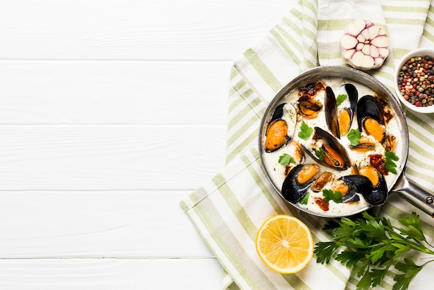 Moules plates en sauce blanche et côtés sur une nappe avec fond Photo gratuit