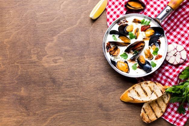 Moules plates en sauce blanche sur une nappe avec fond Photo gratuit
