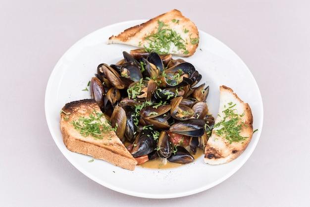 Moules en sauce au persil, pain perdu et citron. fruit de mer. des palourdes dans les coquilles. Photo Premium