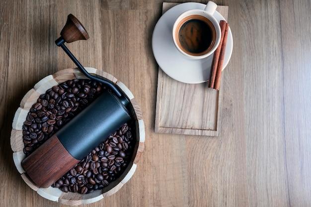 Moulin à café dans un seau en bois avec des grains de café et une tasse d'espresso sur une table en bois Photo Premium