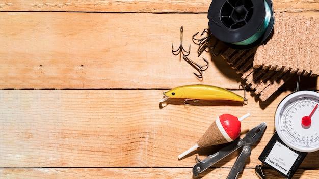Moulinet de pêche; leurre de pêche; flotteur de pêche; pince; tableau de liège et balance sur table Photo gratuit