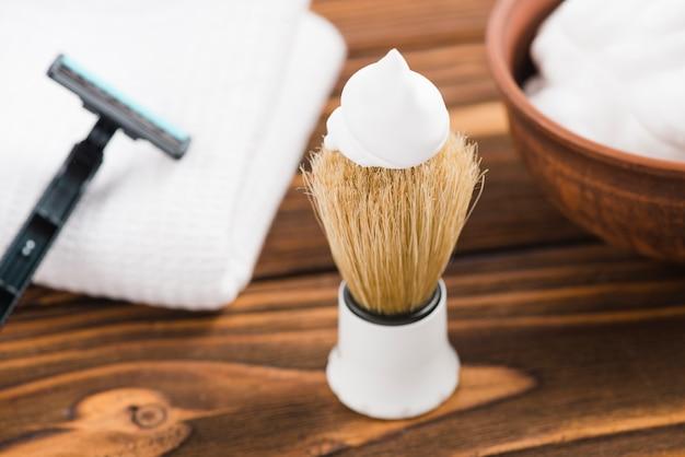 Mousse blanche sur le blaireau avec rasoir; serviette et mousse sur le bureau Photo gratuit