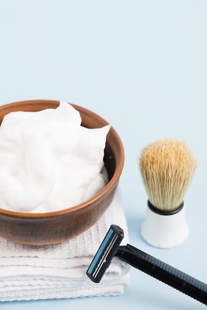 Mousse dans un bol en bois sur une serviette pliée blanche avec blaireau et rasoir sur fond bleu Photo gratuit