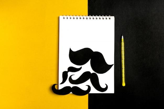 Moustache de papier noir, bloc-notes, stylo, fond jaune Photo Premium
