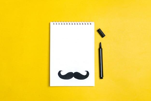 Moustache de papier noir, chapeau, lunettes, bloc-notes sur fond jaune mois dons, concept de la fête des pères Photo Premium