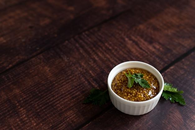 Moutarde à l'assortiment: moutarde de dijon, moutarde cuite et grains secs en terrine dans des bols sur fond en bois Photo Premium