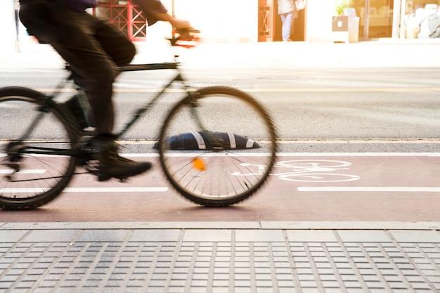 Mouvement flou du cycliste sur la piste cyclable près du trottoir Photo gratuit