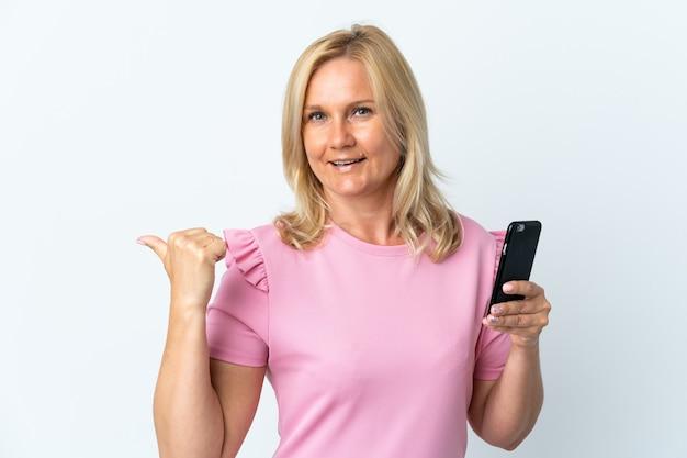 Moyen âge à L'aide De Téléphone Mobile Isolé Sur Un Mur Blanc Pointant Vers Le Côté Pour Présenter Un Produit Photo Premium