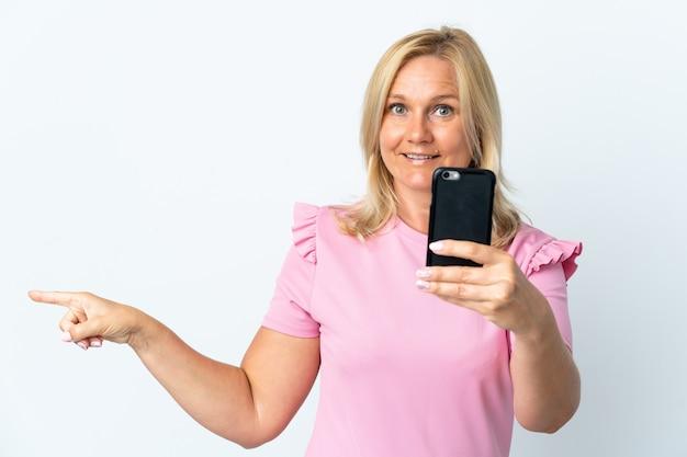 Moyen âge à L'aide De Téléphone Mobile Isolé Sur Un Mur Blanc Surpris Et Pointant Le Doigt Sur Le Côté Photo Premium
