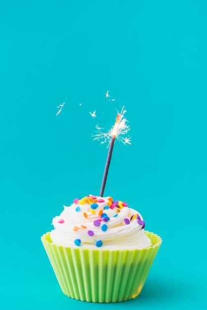 Muffin décoratif avec sparkler illuminé sur fond turquoise Photo gratuit