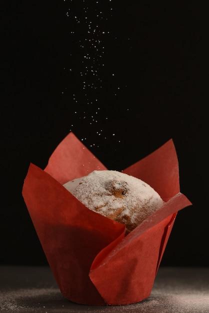 Un muffin en papier sulfurisé rouge se dresse sur une table. Photo Premium