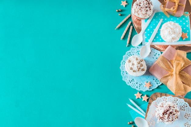 Muffins; accessoires cadeaux et anniversaires sur fond vert Photo gratuit