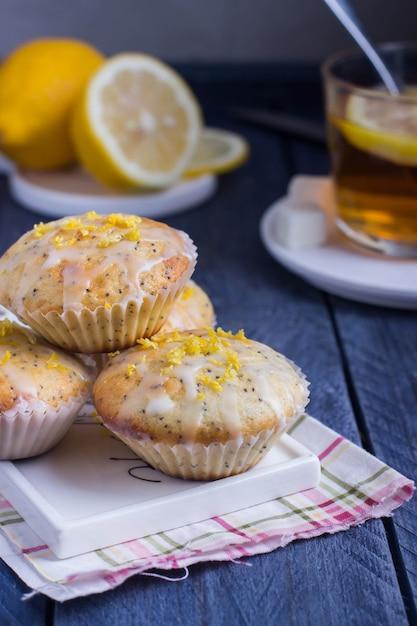 Muffins aromatiques faits maison aux graines de pavot et de pavot avec une tasse de thé sur le fond gris Photo Premium