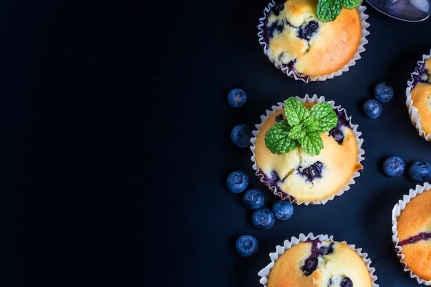 Muffins aux bleuets avec du sucre en poudre et les baies fraîches Photo gratuit
