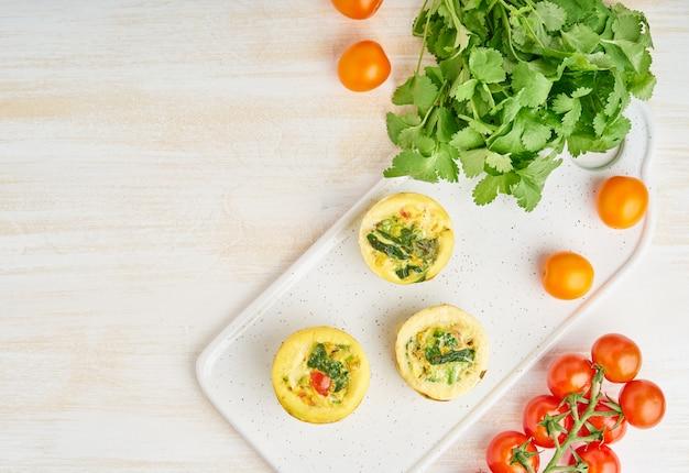 Muffins aux œufs, paléo, régime céto. omelette aux épinards, légumes, tomates Photo Premium