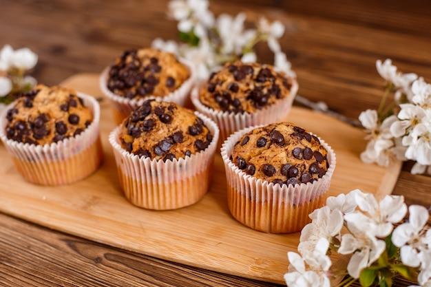Muffins Aux Pépites De Chocolat Et Une Tasse De Café Sur Un Espace En Bois Avec Une Brindille En Fleurs Photo Premium