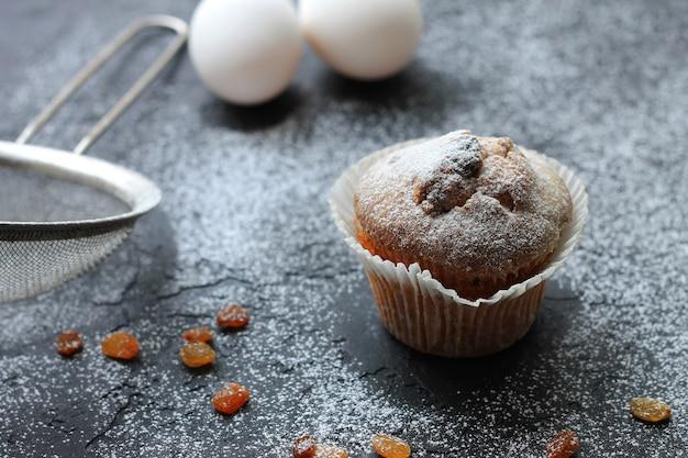 Muffins aux raisins secs saupoudrés de sucre en poudre sur un fond en bois et sont des ingrédients sur un fond flou Photo Premium