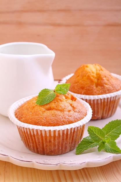 Muffins faits maison décorés à la menthe avec une tasse de thé Photo Premium