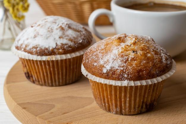 Muffins Frais Faits Maison Avec Du Sucre En Poudre Et Une Tasse De Café Photo Premium