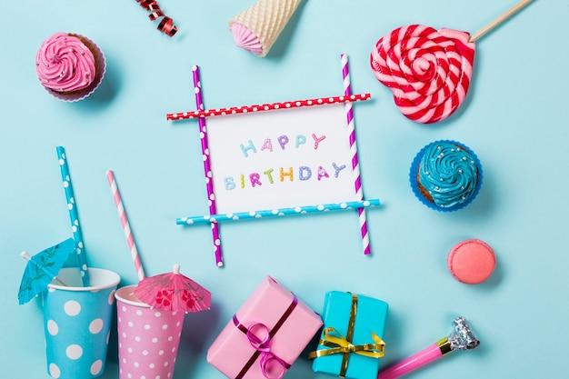 Muffins; macarons; cône de gaufre; coffrets cadeaux et gobelets jetables sur fond bleu Photo gratuit