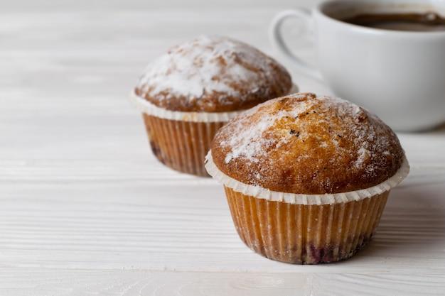 Muffins Maison Fraîchement Préparés Avec Du Sucre En Poudre Et Une Tasse De Café Photo Premium