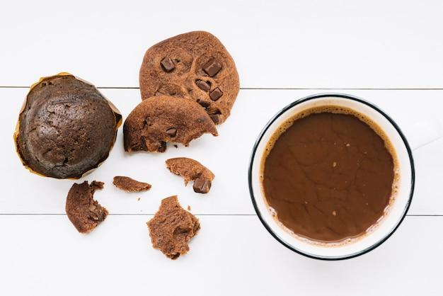 Muffins; mangé des biscuits et du café noir sur la table en bois Photo gratuit
