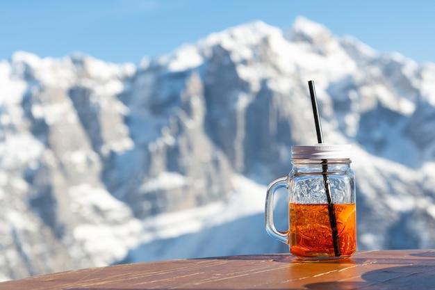 Mug aperol se dresse sur la table d'un café de rue en toile de fond les montagnes. Photo Premium