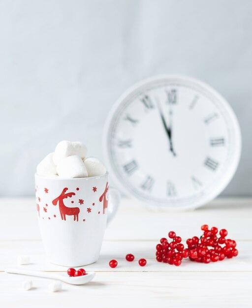 Mug blanc avec boisson chaude et guimauves, baies de viorne rouge, pichet et horloge. Photo Premium