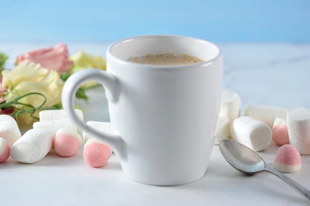 Mug blanc avec fleurs et guimauve Photo Premium