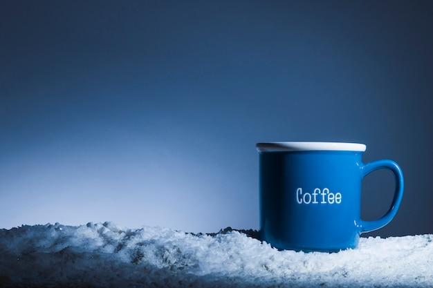 Mug bleu sur la berge de la neige Photo gratuit