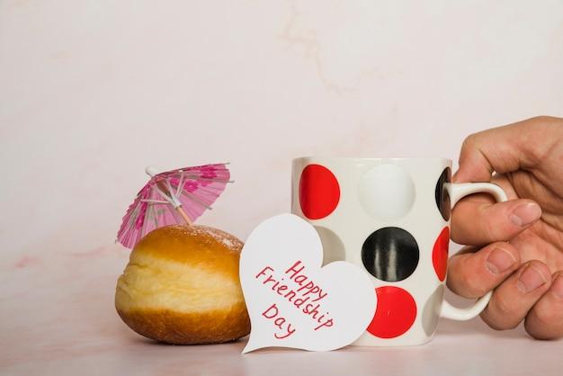 Mug carte postale et beignet Photo gratuit