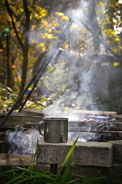 Mug en fer avec boisson chaude près du feu Photo Premium