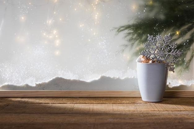Mug avec flocon de neige jouet sur table en bois près de la berge de neige, guirlandes de sapin Photo gratuit