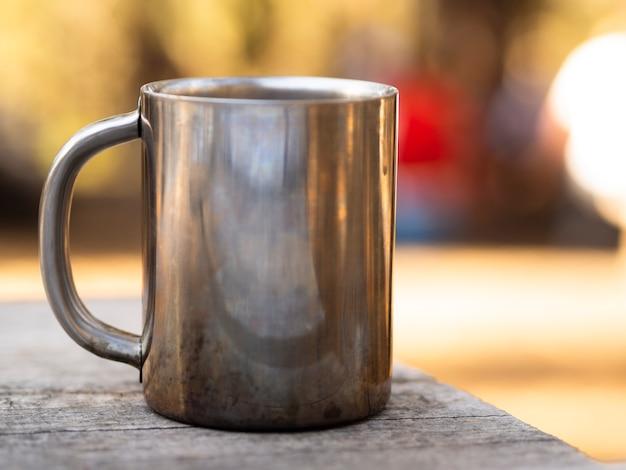 Mug en métal avec des reflets sur une table en bois minable Photo gratuit