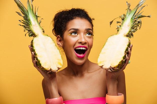 Mulâtre Affamé Avec Maquillage Coloré à La Recherche Vers Le Haut Et Tenant Deux Parties D'ananas Appétissant Frais Isolé, Sur Mur Jaune Photo gratuit
