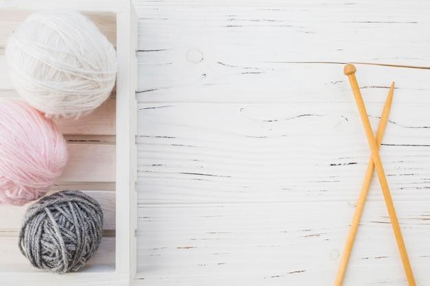 Multi couleur balle de fils près de crochet sur la surface en bois Photo gratuit