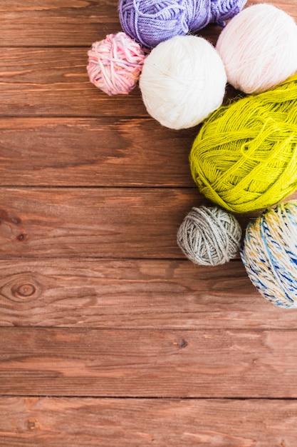 Multi couleur boule de fils sur fond en bois Photo gratuit