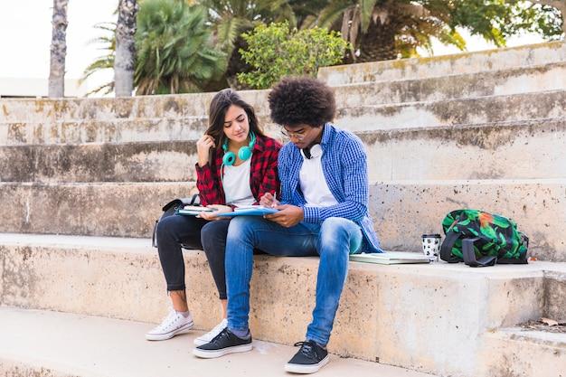 Multi ethnique jeune couple assis sur un escalier étudient ensemble dans le parc Photo gratuit