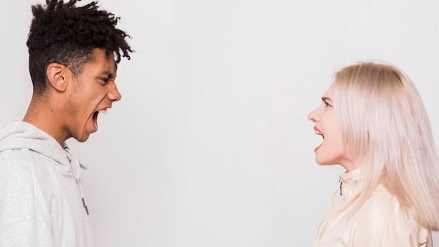 Multi ethnique, jeune, couple, debout, face à face, crier, sur, fond blanc Photo gratuit
