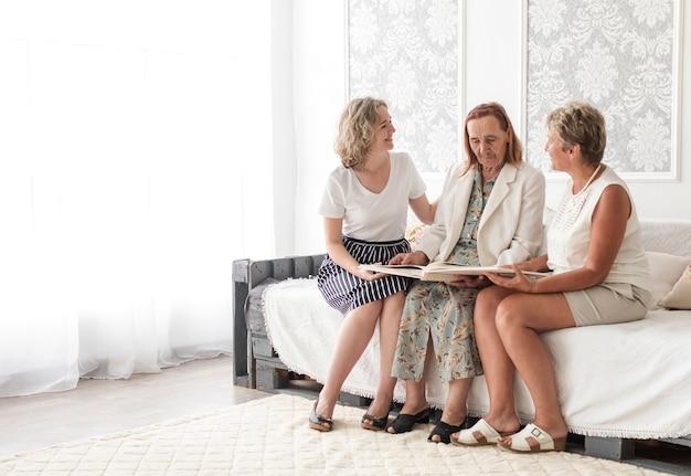 Multi génération femme assise sur un canapé en regardant album photo de famille Photo gratuit