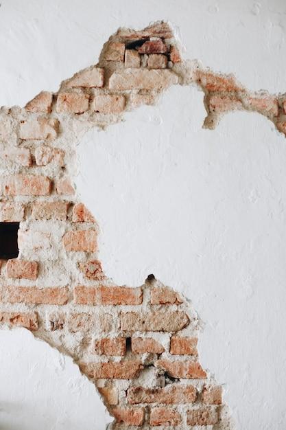 Un mur blanc en béton fissuré avec des briques Photo gratuit
