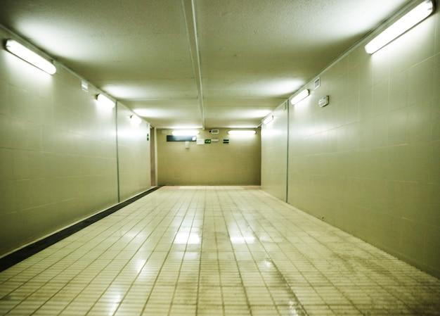 Mur carrelé et tubes de lumière dans la station de métro Photo gratuit