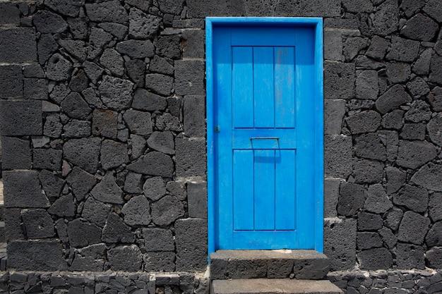 Mur de maçonnerie en pierre de lave de la porte bleue à la palma Photo Premium