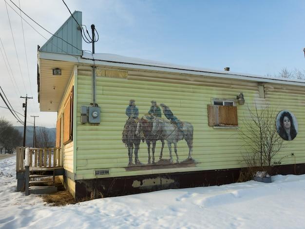 Murale de cowboys sur le mur d'un bâtiment dans la neige, chetwynd, colombie-britannique, canada Photo Premium