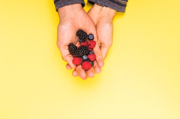 Mûre framboise mûre et cassis appétissant dans les mains sur la surface jaune Photo gratuit