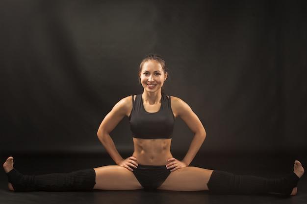 Musculaire Jeune Femme Athlète Assis Dans La Scission Sur Fond Noir Photo gratuit