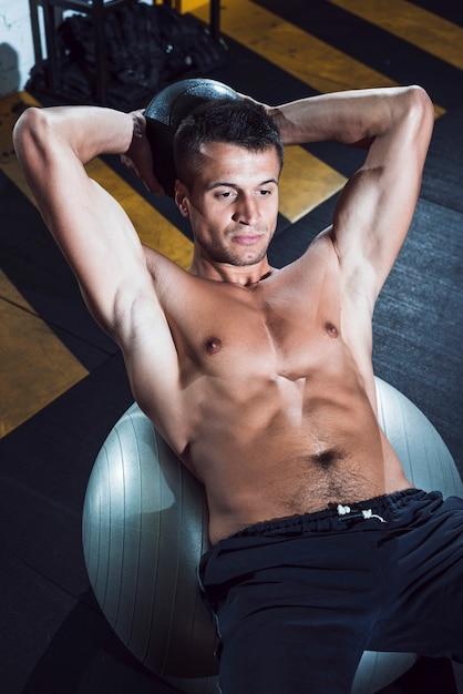 Musculaire jeune homme allongé sur un ballon de fitness Photo gratuit