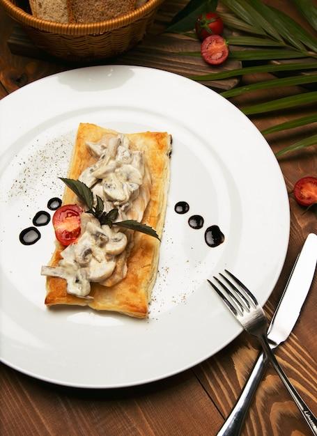 Mushtoom sauté, poulet stroganoff sur un morceau de pain. antipasta dans une assiette blanche décorée avec des couverts sur une table en bois Photo gratuit